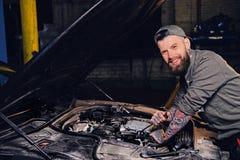 Bearded tattooed mechanics near car in a garage. Portrait of bearded tattooed mechanics near car in a workshop Royalty Free Stock Photo