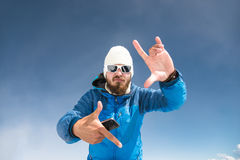 A portrait of a bearded traveler on mountains dancing to the music on the phone and showing the gesture of the camera Stock Images
