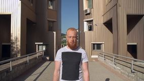 Guy with red hair and beard walk outdoor. Portrait bearded young man focused looking at the camera. businessman walking on the street sunny day summer season. on stock video footage