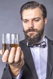 Portrait of a bearded young man with retro look holding a glass Royalty Free Stock Photography