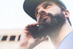 Portrait of bearded young man using his smartphone on the street. Blurred background. Horizontal. Visual effects. Portrait of bearded young man using his Royalty Free Stock Photography