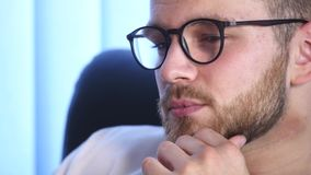 Portrait of a Bearded Young Man Wearing Glasses Sitting in His Office Working on a Computer. Computer Screen Reflects in. His Glasses Stock Images