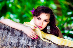 Portrait of the beatiful girl with dangerous snake in the tropical jungle. Royalty Free Stock Image