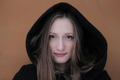 A young beautiful girl with expressive eyes and hood. A portrait of a beautidul girl with expressive eyes, hood and long hair Stock Photo
