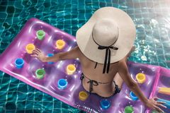 Portrait beautifu woman relaxing in big hat and bikini Sitting b. Ack on air mattress in swimming pool blue water royalty free stock images