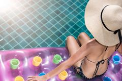 Portrait of beautifu woman relaxing in bikini and big hat in swimming pool. Portrait of beautifu woman relaxing in bikini and big hat sit on air mattress in royalty free stock photo