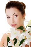 Portrait of beautiful adult woman with health skin and with lily Royalty Free Stock Images