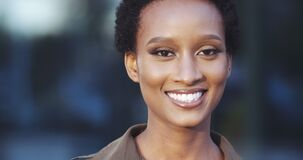 Portrait of beautiful African American ethnic woman looking at camera, smiling toothy, happy eyes, short hair, friendly