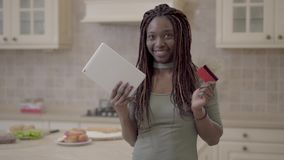 Portrait of beautiful african american smiling woman taking tablet and credit card after successful transaction on