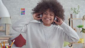 Portrait african american woman with an afro hairstyle listening to music with headphones and dancing. Portrait beautiful african american woman with an afro stock video