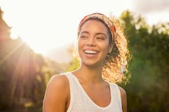 Young african woman smiling at sunset. Portrait of beautiful african american woman smiling and looking away at park during sunset. Outdoor portrait of a smiling royalty free stock photography