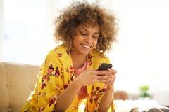Beautiful african american woman using cellphone at home. Portrait of beautiful african american woman using cellphone at home stock photo