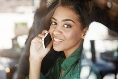 Portrait of beautiful african girl behind glass smiling talking on phone looking at camera. Copy space Royalty Free Stock Photo
