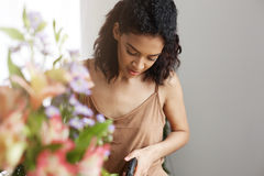 Portrait of beautiful african girl florist smiling looking at camera making flowers bouquet. Portrait of beautiful african girl florist smiling looking at Royalty Free Stock Image
