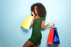 Beautiful african girl happy with shopping bags on blue background. Portrait of beautiful african girl happy with shopping bags on blue background Royalty Free Stock Image