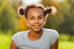 Portrait of beautiful African girl sitting in park royalty free stock photos