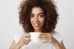 Portrait of beautiful african girl smiling holding cup of coffee looking at camera. White background Royalty Free Stock Photo