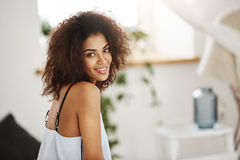 Portrait of beautiful african girl smiling looking at camera. Bedroom background. Royalty Free Stock Photography
