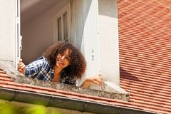 African girl opening shutters of the attic window. Portrait of beautiful African girl teenager opening shutters and looking out the attic window royalty free stock image