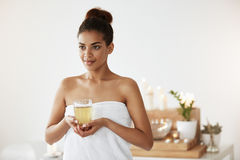 Portrait of beautiful african girl in towel holding glass with tea smiling. Copy space. Spa salon Stock Image