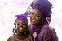 Portrait of beautiful African lady and little girl in traditional dress. Portrait of closeup beautiful African lady and little girl in traditional purple stock photo