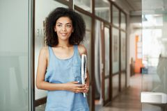 Portrait of beautiful african student girl standing in college corridor smiling holding books looking in side. Education. And learning concept. Copy space Stock Photography