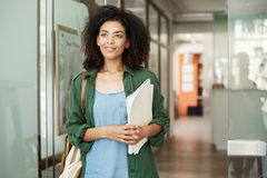 Portrait of beautiful african student girl standing in college corridor smiling holding books looking in side. Education Royalty Free Stock Photo