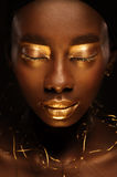 Portrait of beautiful african woman with creative gold make–up and jewelry. Close up portrait of beautiful african woman with creative gold make–up and Stock Image