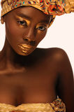 Portrait of beautiful african woman with creative gold make–up and turban. Close up portrait of beautiful african woman with creative gold make–up and turban Stock Photo