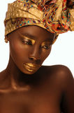 Portrait of beautiful african woman with creative gold make–up and turban. Close up portrait of beautiful african woman with creative gold make–up and turban Stock Image