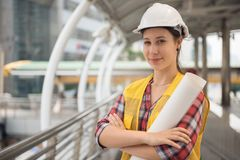 Portrait of Beautiful American woman engineer in town. Portrait of Beautiful American young woman engineer with white helmet hat and engineer paper blueprint stock photography