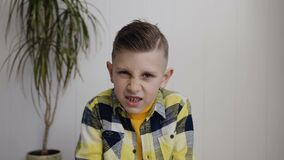 Portrait of beautiful angered 7- 8 years boy who sits on the floor over white wall background. Boy making angry face and. Shows a fist at the camera, slow stock video footage