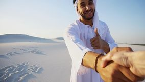 Portrait of beautiful Arabian Sheikh Emirate male tourist guide,. Cheerful Arab male with kindly smile on face leads woman`s arm from camera and shows desert Stock Photo