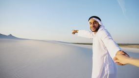 Portrait of beautiful Arabian Sheikh Emirate male tourist guide,. Cheerful Arab male with kindly smile on face leads woman`s arm from camera and shows desert Royalty Free Stock Photos