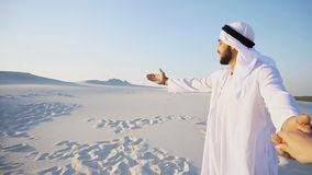 Portrait of beautiful Arabian Sheikh Emirate male tourist guide,. Cheerful Arab male with kindly smile on face leads woman`s arm from camera and shows desert Stock Photography