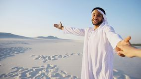 Portrait of beautiful Arabian Sheikh Emirate male tourist guide,. Cheerful Arab male with kindly smile on face leads woman`s arm from camera and shows desert Royalty Free Stock Photography