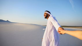 Portrait of beautiful Arabian Sheikh Emirate male tourist guide, who holds woman`s hand and conducts dialogue, walks. Cheerful Arab male with kindly smile on stock video footage