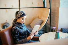 Beautiful Arabic Muslim girl using tablet in cafe. Portrait of beautiful Arabic Muslim girl using tablet in cafe Stock Photo