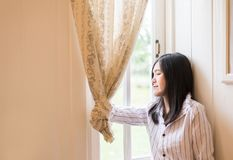 Portrait of beautiful asian female relax and standing near window at home,Positive thinking,Good attitude,Close your eyes. Portrait of beautiful asian woman royalty free stock photo