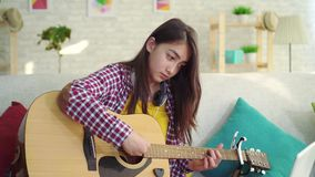 Beautiful asian girl with long hair in the living room of modern home with acoustic guitar watching training online on. Portrait of beautiful asian girl with stock footage