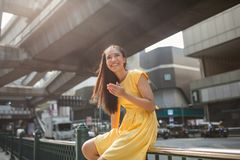 Portrait of a beautiful asian girl outdoors. The girl sits on the railing near a busy street and smiles, looking away. She is wearing a yellow dress royalty free stock images