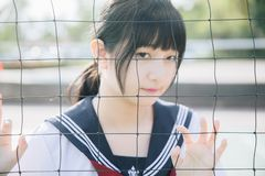 Portrait of beautiful Asian japanese high school girl uniform looking with net in green background. Portrait of beautiful Asian japanese high school girl uniform royalty free stock photography