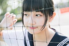 Portrait of beautiful Asian japanese high school girl uniform looking with net in green background. Portrait of beautiful Asian japanese high school girl uniform stock photo