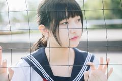 Portrait of beautiful Asian japanese high school girl uniform looking with net in green background. Portrait of beautiful Asian japanese high school girl uniform stock photography