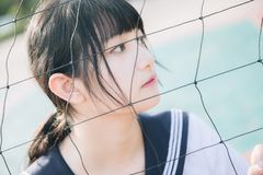 Portrait of beautiful Asian japanese high school girl uniform looking with net in green background. Portrait of beautiful Asian japanese high school girl uniform royalty free stock images