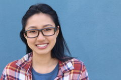 Portrait of beautiful Asian teen girl smiling, with wayfarers, isolated on blue background with copy space on the right Royalty Free Stock Image