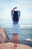 A portrait of beautiful asian woman in dress back stand and rise hands on a stone by the sea