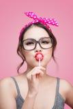 Portrait of beautiful asian woman eating heart shape lollipop, d Royalty Free Stock Photo