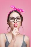 Portrait of beautiful asian woman eating heart shape lollipop, d Stock Images