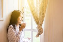 Portrait of beautiful asian woman is holding a cup of coffee and looking something on window at home in the morning,Happy and smil royalty free stock photos